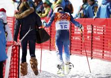 Bode Miller of the U.S. (R) leave the venue with his wife Morgan Beck after the men's alpine skiing giant slalom event at the 2014 Sochi Winter Olympics at the Rosa Khutor Alpine Center February 19, 2014. REUTERS/Mike Segar
