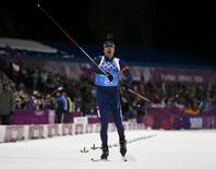 Norway's Emil Hegle Svendsen celebrates as he crosses the finish line to win the mixed biathlon relay at the Sochi 2014 Winter Olympics February 19, 2014. REUTERS/Stefan Wermuth