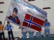 Болельщик размахивает флагом с фотографией Уле Эйнара Бьерндалена во время цветочной церемонии по итогам смешанной эстафеты на Олимпиаде в Сочи. Норвежский биатлонист Уле Эйнар Бьерндален выиграл в среду вместе с партнерами по команде смешанную эстафету на Играх в Сочи и завоевал 13-ю медаль на зимних Олимпиадах, превзойдя рекорд своего соотечественника, легендарного лыжника Бьерна Дэли. REUTERS/Carlos Barria