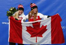 Canada's pilot Kaillie Humphries and Heather Moyse (R) celebrate with a national flag during the flower ceremony for the women's bobsleigh event at the Sochi 2014 Winter Olympics February 19, 2014. Canada 1 finished first ahead of United States 1 and United States 2. REUTERS/Arnd Wiegmann