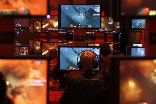 Visitors play a video game at an exhibition stand during the Gamescom 2011 fair in Cologne, August 17, 2011. REUTERS/Ina Fassbender