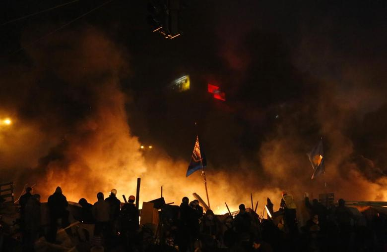 Anti-government protesters stand behind burning barricades in Kiev's Independence Square February 19, 2014. REUTERS/Yannis Behrakis