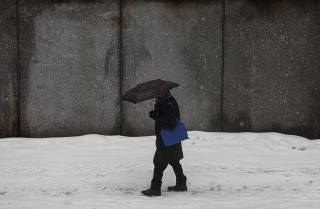 A man walks through the snow in New York February 18, 2014. REUTERS/Eric Thayer