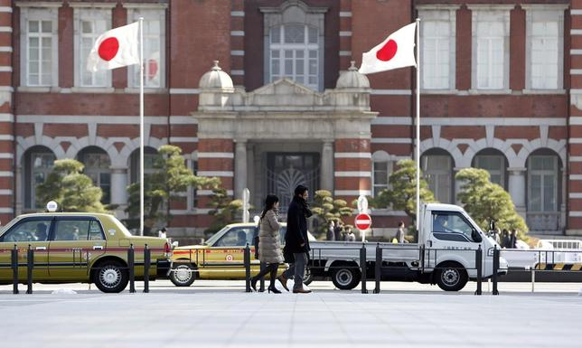 Pedestrians walk under Japan's national flags outside the Tokyo Station February 17, 2014. REUTERS/Yuya Shino
