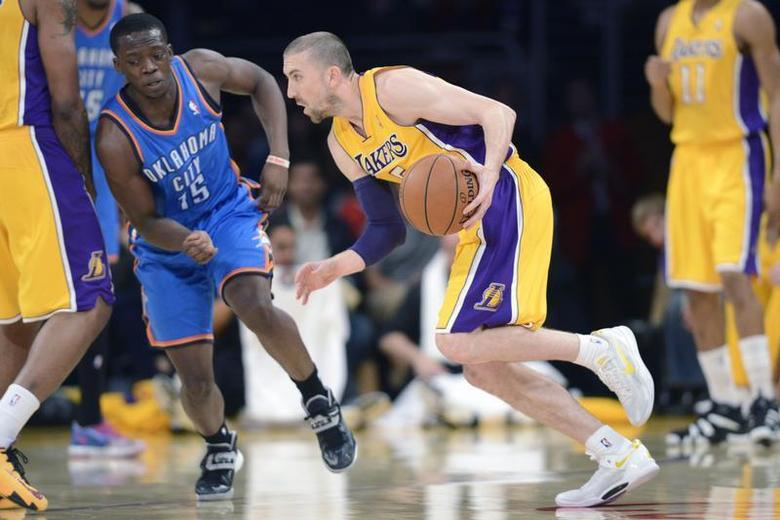 Feb 13, 2014; Los Angeles, CA, USA; Los Angeles Lakers guard Steve Blake (5) handles the ball defended by Oklahoma City Thunder guard Reggie Jackson (15) during the first quarter at the Staples Center. Mandatory Credit: Kelvin Kuo-USA TODAY Sports - RTX18SBM