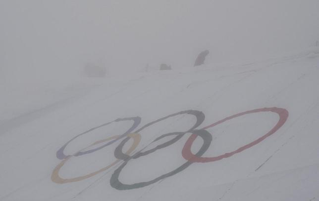 A man walks behind the Olympic rings ahead of the men's snowboard cross qualification round at the 2014 Sochi Winter Olympic Games in Rosa Khutor February 17, 2014. REUTERS/Dylan Martinez