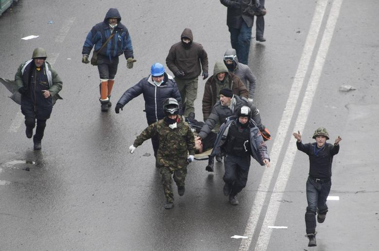 Anti-government protesters run with an injured man on a stretcher in Independence Square in Kiev February 20, 2014. REUTERS/Vasily Fedosenko