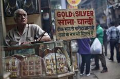 Торговец ювелирными изделиями из золота и серебра стоит в ожидании покупателей на улице в Дели 7 октября 2013 года. Цены на золото растут по мере снижения курса доллара и повышения спроса на физическом рынке. REUTERS/Mansi Thapliyal