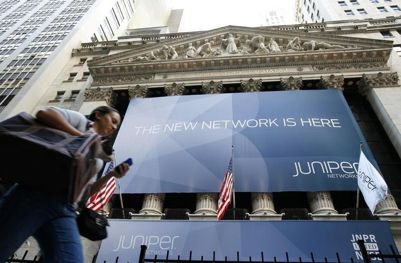 A woman walks past a banner with the logo of Juniper Networks Inc. covering the facade of the New York Stock Exchange, October 29, 2009. REUTERS/Brendan McDermid/Files