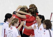 Britain's curling team celebrates with a group hug after winning in their women's bronze medal curling game against Switzerland (foreground) at the Ice Cube Curling Centre during the Sochi 2014 Winter Olympics February 20, 2014. REUTERS/Ints Kalnins