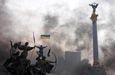 Участник антиправительственных протестов с флагом Украины на статуе в центре Киева 20 февраля 2014 года. Российский фондовый рынок сохраняет в четверг пессимистичный настрой на фоне кровопролития на Украине, ослабления рубля и бегства из рисковых активов на развивающихся площадках, но массовых распродаж местных акций участники торгов не наблюдают. REUTERS/Stringer