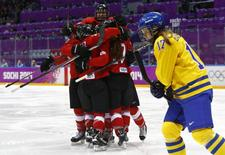 Хоккеистки сборной Швейцарии радуются шайбе, заброшенной в ворота сборной Швеции в матче за третье место на олимпийском турнире в Сочи 20 февраля 2014 года. Женская сборная Швейцарии по хоккею завоевала бронзовую медаль сочинской Олимпиады, обыграв в финале команду Швеции. REUTERS/Mark Blinch