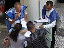 Unos promotores de empleo entregan volantes a unas personas en una calle del centro de Sao Paulo, mar 25 2011. - La tasa de desempleo de Brasil subió menos a lo esperado en enero debido a que un continuo declive en el número de personas que buscan trabajo ayudó a contrarrestar una creación de empleo más débil. REUTERS/Paulo Whitaker