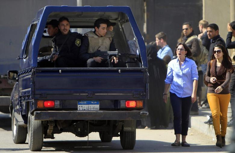 Foreign journalists and relatives of Al-Jazeera journalists walk near a police vehicle outside Cairo's Tora prison, where the trial of Al Jazeera journalists and other foreign media is due to take place, February 20, 2014. REUTERS/Amr Abdallah Dalsh