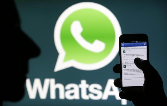A Whatsapp App logo is seen behind a Samsung Galaxy S4 phone that is logged on to Facebook in the central Bosnian town of Zenica, February 20, 2014. REUTERS/Dado Ruvic