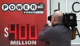 A TV cameraman films a sign for Virginia's $400 million Powerball lottery in Arlington, Virginia February 19, 2014. REUTERS/Kevin Lamarque