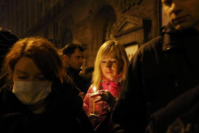 A woman holds a candle as she attends the transfer of over a dozen of corpses from a hotel lobby to a local hospital following clashes with riot police at Independence Square in Kiev February 20, 2014. REUTERS/Yannis Behrakis