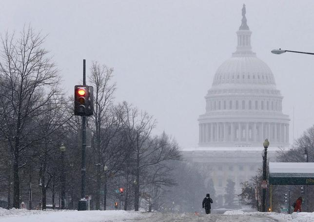 A pedestrian walks up the middle of North Capitol Street towards the U.S. Capitol building, on largely deserted streets, as a major snow storm hits the Washington area closing U.S. Federal Government offices for the day and shutting down much of the city of Washington February 13, 2014. REUTERS/Jim Bourg (