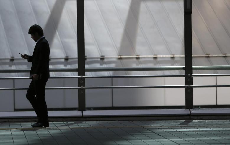 A man holding his mobile phone walks on an overpass at Tokyo's business district February 20, 2014. REUTERS/Yuya Shino
