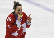 Canada's Marie-Philip Poulin bites her gold medal during the presentation ceremony after her team defeated Team USA in overtime in the women's ice hockey final game at the 2014 Sochi Winter Olympics, February 20, 2014. REUTERS/Gary Hershorn