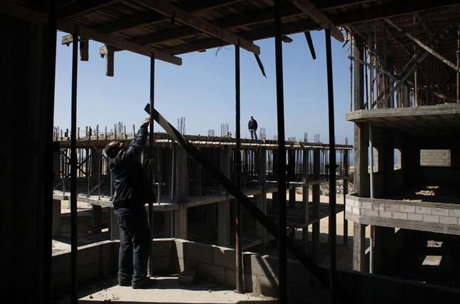Palestinians inspect a building under construction, where work was stopped, in the southern Gaza Strip February 19, 2014. REUTERS/Ibraheem Abu Mustafa