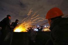Антиправительственные демонстранты греютяс у костра на Майдане Незалежности в Киеве 21 февраля 2014 года. Ночные переговоры об урегулировании кровопролитного политического кризиса на Украине были прерваны ранним утром, после чего западные посредники сказали, что они продолжатся днем, а президент Виктор Янукович объявил, что уже в полдень готовится подписать согласованный документ. REUTERS/Yannis Behrakis