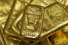 Слитки золота в хранилище отделения трейдера Degussa в Цюрихе 19 апреля 2013 года. Цены на золото снижаются под давлением растущего доллара, но вырастут третью неделю подряд, так как инвесторы видят нестабильный рост мировой экономики. REUTERS/Arnd Wiegmann