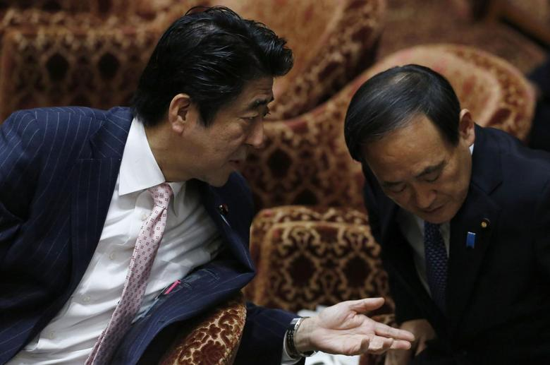 Japan's Prime Minister Shinzo Abe (L) speaks to Chief Cabinet Secretary Yoshihide Suga before Suga answers questions during a lower house budget committee session at the parliament in Tokyo February 20, 2014. REUTERS/Yuya Shino
