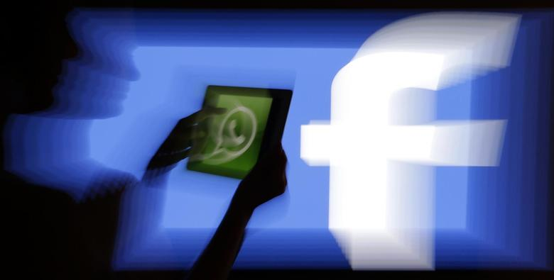 A woman holds a tablet displaying WhatsApp's logo in front of the screen with the Facebook logo in this photo illustration taken in Prague February 20, 2014. REUTERS/David W Cerny
