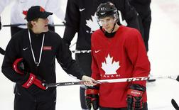 Canada's men's ice hockey team captain Sidney Crosby (R) listens to head coach Mike Babcock give directions during a team practice at the 2014 Sochi Winter Olympics, February 18, 2014. REUTERS/Jim Young