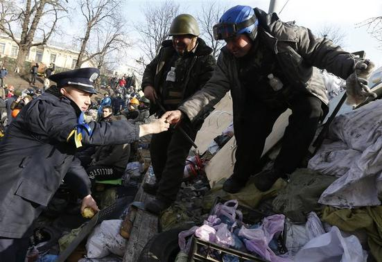 A policeman from Lviv (L), who has joined anti-government protesters, visits barricades in Kiev February 21, 2014. REUTERS-Vasily Fedosenko
