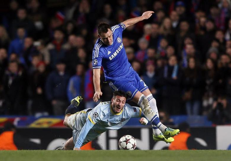 Chelsea's John Terry (R) challenges Steaua Bucharest's Pantelis Kapetanos during their Champions League soccer match at Stamford Bridge in London December 11, 2013. REUTERS/Stefan Wermuth