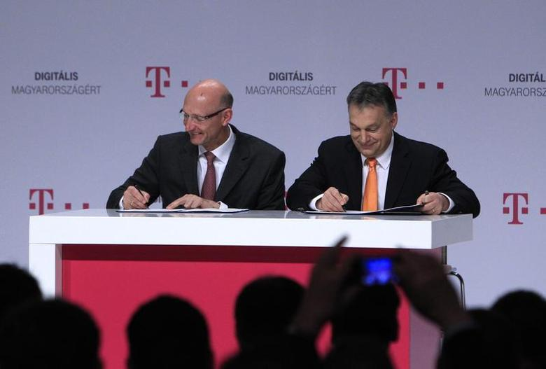 Hungarian Prime Minister Viktor Orban (R) and Chief Executive of Deutsche Telekom Timotheus Hottges (L) sign an agreement during a news conference in Budapest, February 21, 2014. REUTERS/Bernadett Szabo
