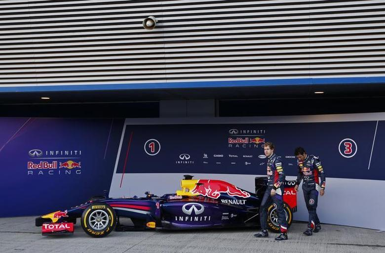 Red Bull Formula One drivers Sebastian Vettel (L) of Germany and Daniel Ricciardo of Australia walks after unveiling the new RB10 during the official presentation of the Red Bull Formula One Team 2014 at the Jerez racetrack in southern Spain January 28, 2014. REUTERS/Marcelo del Pozo