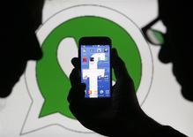 Una persona sostiene un teléfono móvil con el logo de Facebook como papel mural detrás de un logo de la firma de mensajería Whatsapp en Zenica, Bosnia-Herzegovina, feb 20 2014. En los últimos años, una serie de aplicaciones de mensajería han luchado por lograr un lugar dominante a nivel mundial, y muchas se jactaban de una lucrativa combinación de herramientas de comunicación, compras online y juegos. REUTERS/Dado Ruvic