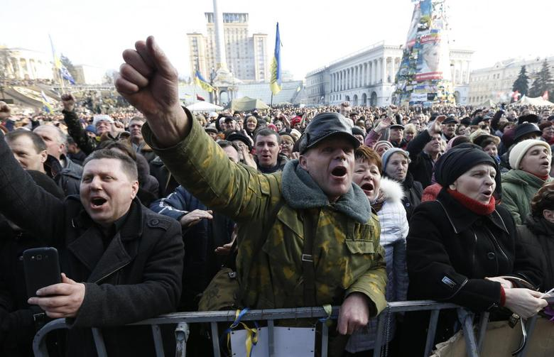 People cheer as they listen to speeches in front of a statue in Independence Square in Kiev February 21, 2014. REUTERS/Vasily Fedosenko