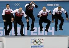 Канадские керлингисты Калеб Флэкси, Райан Харнден, И Джэй Харнден, Райан Фрай и Брэд Джейкобс (слева направо) на пьедестале после победы в финальном матче на Олимпиаде в Сочи 21 февраля 2014 года. Канадские керлингисты в пятницу выиграли финальный матч у Великобритании, повторив достигнутый днем ранее успех своих соотечественниц. REUTERS/Ints Kalnins