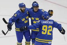 Sweden's Henrik Zetterberg (40) celebrates his goal with teammates Alexander Steen (20) and Gabriel Landeskog (92) during the second period of their men's preliminary round hockey game against the Czech Republic at the Sochi 2014 Winter Olympic Games, February 12, 2014. REUTERS/Grigory Dukor