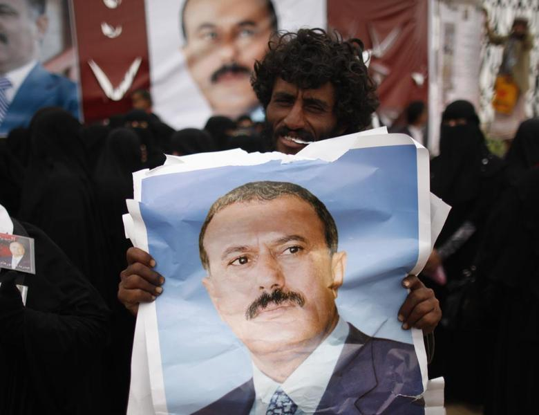 A man holds a poster of Yemen's former President Ali Abdullah Saleh outside al-Saleh mosque after weekly Friday prayers in Sanaa May 17, 2013 file photo. REUTERS/Khaled Abdullah