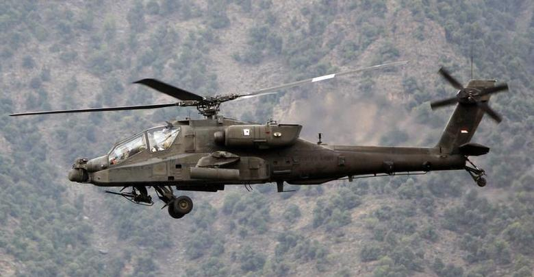 A U.S. military AH-64 Apache assault helicopter flies past a bunker of U.S. soldiers from Task Force ''No Fear'' 3rd Platoon, 2-27 Infantry ''The Wolfhounds'', after engaging in firefights with the Taliban, in Ghaziabad district in Kunar, Afghanistan September 15, 2011. REUTERS/Erik De Castro