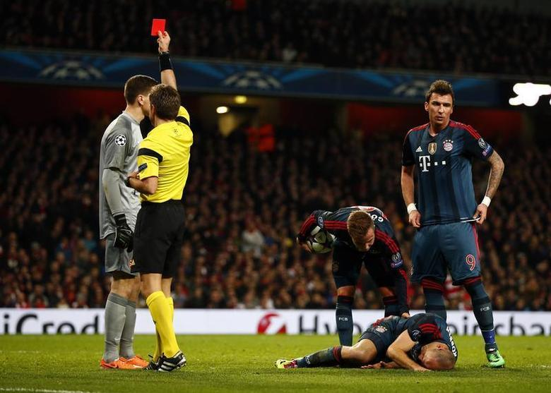 Arsenal's goalkeeper Wojciech Szczesny (L) receives a red card from referee Nicola Rizzoli after a foul against Bayern Munich's Arjen Robben (bottom R) during their Champions League round of 16 first leg soccer match at the Emirates Stadium in London February 19, 2014. REUTERS/Darren Staples
