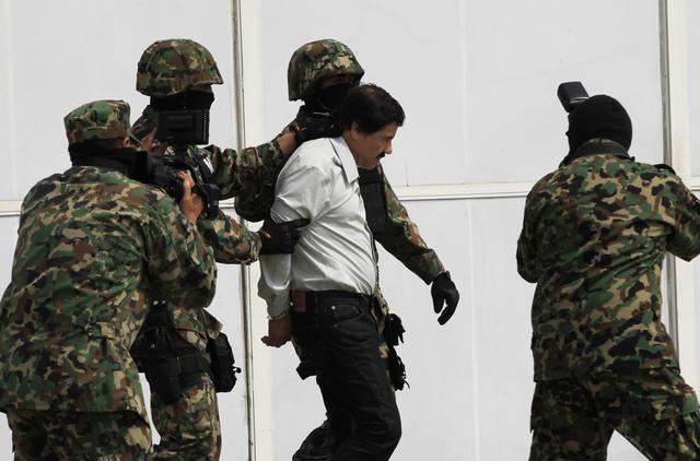 Joaquin ''Shorty'' Guzman is escorted by soldiers during a presentation at the Navy's airstrip in Mexico City February 22, 2014. REUTERS/Henry Romero