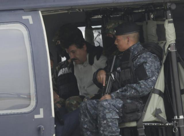 Joaquin ''Shorty'' Guzman (C) is seen sitting inside a Mexican federal police helicopter at the Navy's airstrip in Mexico City February 22, 2014. REUTERS/Henry Romero
