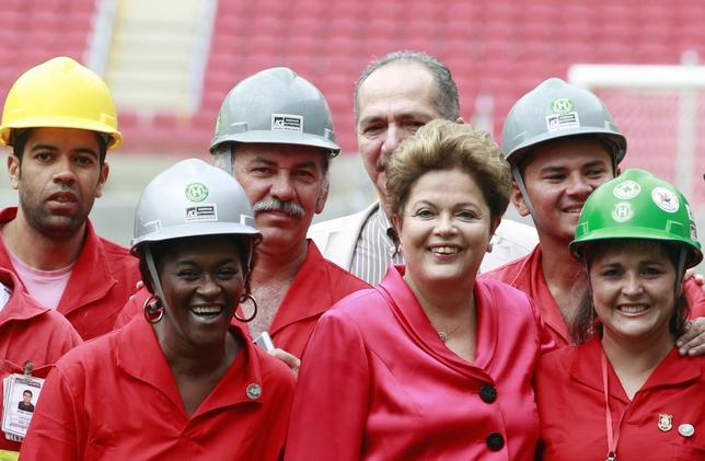 Brazil's President Dilma Rousseff (3rd R) poses with workers during the opening ceremony of the Beira-Rio stadium, which will be one of the stadiums hosting the 2014 World Cup soccer matches, in Porto Alegre February 20, 2014. REUTERS/Edison Vara