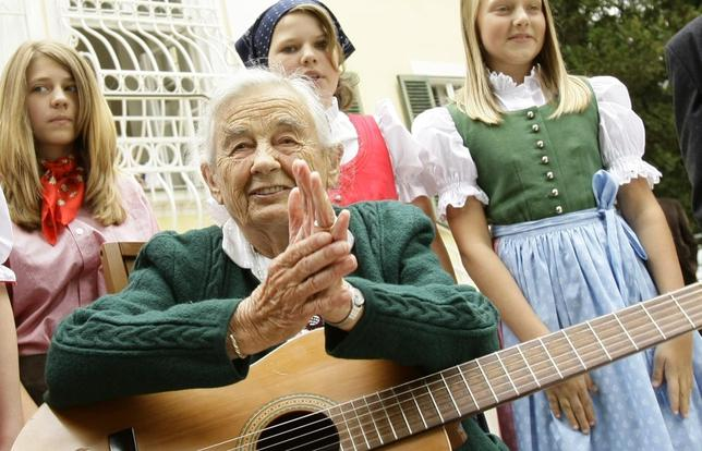 Maria von Trapp, daughter of Austrian Baron Georg von Trapp, prepares to play a guitar and sing with traditionally dressed children in front of her former home, Villa Trapp, in Salzburg in this July 24, 2008 file photo. REUTERS/Leonhard Foeger/Files