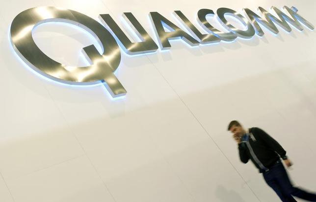 A man walks past a Qualcomm advertising logo at the Mobile World Congress at Barcelona, February 27, 2013. The GSMA Mobile World Congress, representing the interests of the worldwide mobile communications industry, takes place from February 25 to 28 in Barcelona. REUTERS/Albert Gea/Files