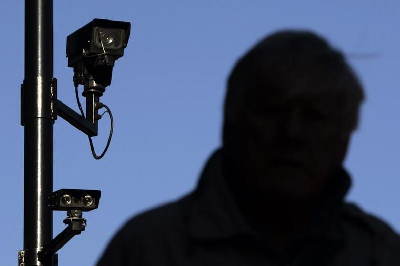 A security camera overlooks a man as he walks down a street in London November 2, 2006. REUTERS/Luke MacGregor