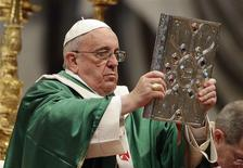 Pope Francis holds the Book of the Gospels as he celebrates a mass in Saint Peter's Basilica at the Vatican February 23, 2014. REUTERS/Max Rossi