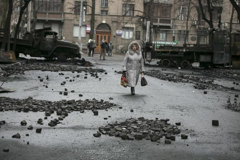 A woman walks past burnt trucks near parliament house in Kiev February 23, 2014. REUTERS/Baz Ratner