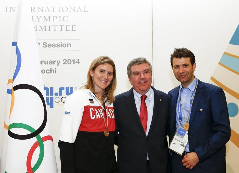 International Olympic Committee (IOC) President Thomas Bach (C) pose with newly elected members of the IOC, Canada's Hayley Wickenheiser (L) and Norway's Ole Einar Bjoerndalen, at the IOC session on the final day of the Sochi 2014 Olympic Winter Games in Sochi February 23, 2014. REUTERS/Shamil Zhumatov